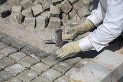 Colocación de los adoquines naturales de la piedra del granito en arena Fotos de archivo libres de regalías