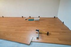 Colocación del piso y de las herramientas de madera durante renovaciones imagenes de archivo