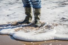 Colocación en agua en la playa con los wellies Fotografía de archivo libre de regalías