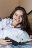 Colocación femenina joven emocionante con el libro abierto encendido Foto de archivo libre de regalías