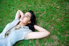 Colocación femenina joven en la hierba, pensando Imágenes de archivo libres de regalías