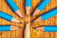 Colocación hacia fuera de la muchedumbre con los lápices de madera en el escritorio Imagen de archivo libre de regalías