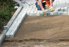 Colocación pavimentando ladrillos en suelo Imagen de archivo libre de regalías