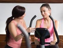 Colocación que se sienta de la bici del instructor de gimnasio de dos mujeres que escucha que habla Fotos de archivo
