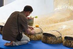 Colocación del oro en el pie de Buddha Foto de archivo libre de regalías