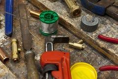 Colocaciones de la llave ajustable y de la fontanería en un banco de trabajo Foto de archivo libre de regalías