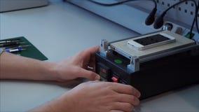 Colocan al individuo de las TIC hacer mantenimiento un teléfono con una pantalla quebrada en el elemento de calefacción almacen de metraje de vídeo