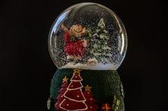 Colocan a Santa Claus en una bola en un fondo negro imagen de archivo libre de regalías