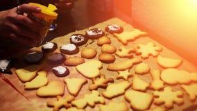 Colocando decorações em cookies recentemente cozidas do Natal filme