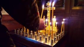 Colocando a gente de las velas pida a dios perdón y bienestar Caras santas en el icono en un fondo almacen de video