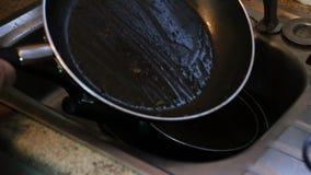 Colocando platos sucios en fregadero para lavarse para arriba metrajes