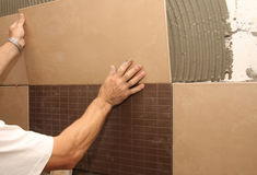 Colocando a telha cerâmica na parede Fotos de Stock Royalty Free