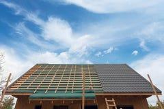Colocando a telha do metal no telhado Casa sob a construção com ferro da chave de fenda e do telhado Fotografia de Stock Royalty Free