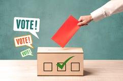 Colocando um deslizamento de votação em uma urna de voto Imagem de Stock