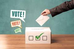 Colocando um deslizamento de votação em uma urna de voto Imagens de Stock