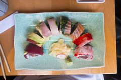Dragon roll Susi lunch or dinner. Coloerful Susi cut dragon rolls placed on green retangle plate like a rainbow stock images