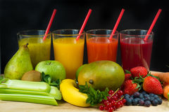 Colofrul fresh pressed fruit juices in tall glasses with fruits Royalty Free Stock Images