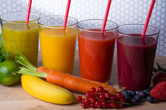 Colofrul fresh pressed fruit juices in tall glasses with fruits Stock Photography