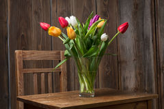 Coloful tulips in a vase. On a wooden table stock photography
