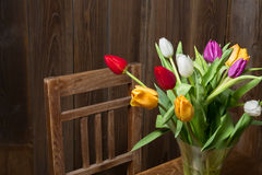 Coloful tulips in a vase. On a wooden table royalty free stock photo