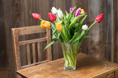 Coloful tulips in a vase. On a wooden table royalty free stock photography