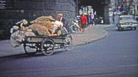 COLOGNE, ALLEMAGNE - 1966 : Un pauvre homme faisant du vélo une grande quantité de marchandises inconnues à travers la ville banque de vidéos