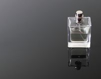 Cologne bottle. Cube shapped cologne bottle, top off, on smoked, glass table stock photos