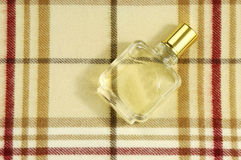 Cologne bottle on check pattern. Bottle of cologne on colorful checkered pattern with plenty of copyspace for advertising text stock photos