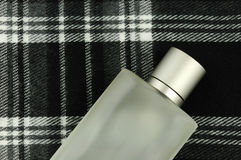Cologne bottle on check pattern. Bottle of cologne on black and white checkered pattern with plenty of copyspace for advertising text stock image