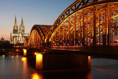 Cologne Cathedral. The Cologne Cathedral is a UNESCO world heritage site. Seen here together with the illuminated Hohenzollern bridge stock photo