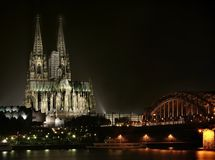 Cologne Cathedral. At night with Hohenzollern Bridge on the right royalty free stock image