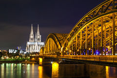 Cologne Cathedral with the Hohenzollern bridge at night Stock Photos