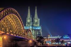 Cologne Cathedral and Hohenzollern Bridge at Night. Cologne`s famous cathedral and the Hohenzollern Bridge illuminated at night Royalty Free Stock Photos