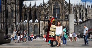 Cologne Cathedral. A man dressed like a Roman soldier is posing in front of Cologne Cathedral. Cologne Cathedral (High Cathedral of St. Peter) is a Roman stock photography
