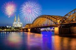 Cologne domkyrka och Hohenzollern bro med fyrverkerier arkivbild