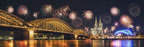 Cologne domkyrka och Hohenzollern bro med fyrverkerier på nytt royaltyfri bild