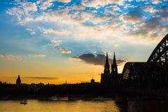 Cologne domkyrka och hohenzollern bro på solnedgången arkivfoton