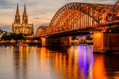 Cologne domkyrka och Hohenzollern bro på solnedgången, Tyskland arkivbild