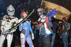 Three cosplayer are posing with weapons at the trade fair Gamesc Royalty Free Stock Photos