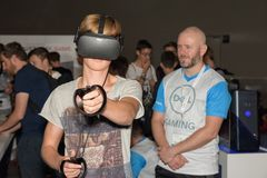 A visitor is playing a virtual reality game with oculus rift. Cologne, Germany - August 24, 2017: A visitor is playing a virtual reality game with oculus rift + Royalty Free Stock Images
