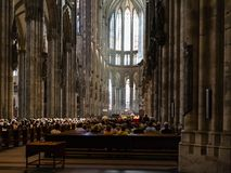 Visitors in church service in Cologne Cathedral. COLOGNE, GERMANY - JUNE 27, 2010: visitors in church service in Cologne Cathedral. The Cathedral is Germany`s stock photo