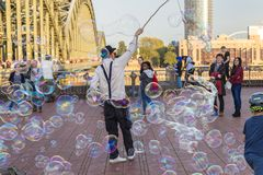 COLOGNE, GERMANY- OCTOBER 06, 2018: Walking tourists watching a guy blowing bubbles. stock photos