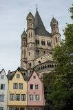 COLOGNE, GERMANY - SEPTEMBER 11, 2016: Colorful houses in Bavarian style and the Romanesque Catholic church `Gross Sankt Martin` Stock Image