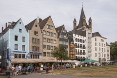COLOGNE, GERMANY - SEPTEMBER  11, 2016: Colorful houses in Bavarian style and the Romanesque Catholic church `Gross Sankt Martin` Stock Images