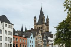 COLOGNE, GERMANY - SEPTEMBER  11, 2016: Colorful houses in Bavarian style and the Romanesque Catholic church `Gross Sankt Martin` Royalty Free Stock Image