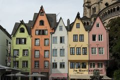 COLOGNE, GERMANY - SEPTEMBER 11, 2016: Colorful houses in Bavarian style and the Romanesque Catholic church `Gross Sankt Martin` Royalty Free Stock Photo