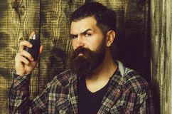 Cologne for men. Brutal man applying perfume or cologne from black bottle. Cologne for men. perfume. Brutal man or bearded caucasian hipster with grey hair, long stock image