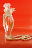 Cologne/perfume bottles against orange background. Bottle with spirits on a red background and a thread with white pearls Stock Photo