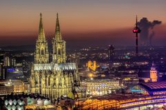 Cologne Cathedral illuminated at night. Cologne`s famous cathedral and the railway station of Cologne, illuminated at night Royalty Free Stock Image