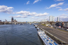 Cologne skyline with dome and bridge and ships on pier Stock Image